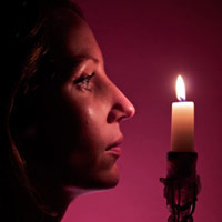A girls profile facing a lighted candle