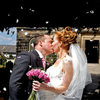 A newly wedded couple kiss in front of the church